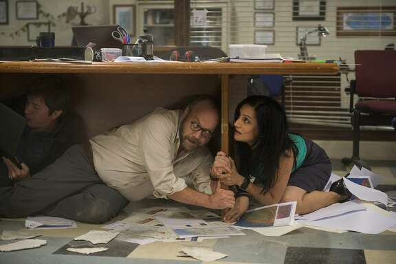 "This photo provided by Warner Bros. Pictures shows Paul Giamatti as Lawrence and Archie Panjabi as Serena, in a scene from the action thriller, ""San Andreas."" The movie releases in theaters on May 29, 2015.  (Jasin Boland/Warner Bros. Pictures via AP)"