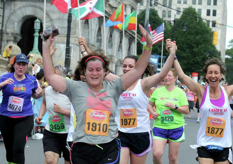 Runners celebrate as they cross the finish line during the 37th Annual Freihofer's Run for Women on Saturday May 30, 2015 in Albany, N.Y.  (Michael P. Farrell/Times Union) Photo: Michael P. Farrell / 00032011A