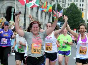 Runners celebrate as they cross the finish line during the 37th Annual Freihofer's Run for Women on Saturday May 30, 2015 in Albany, N.Y.  (Michael P. Farrell/Times Union)