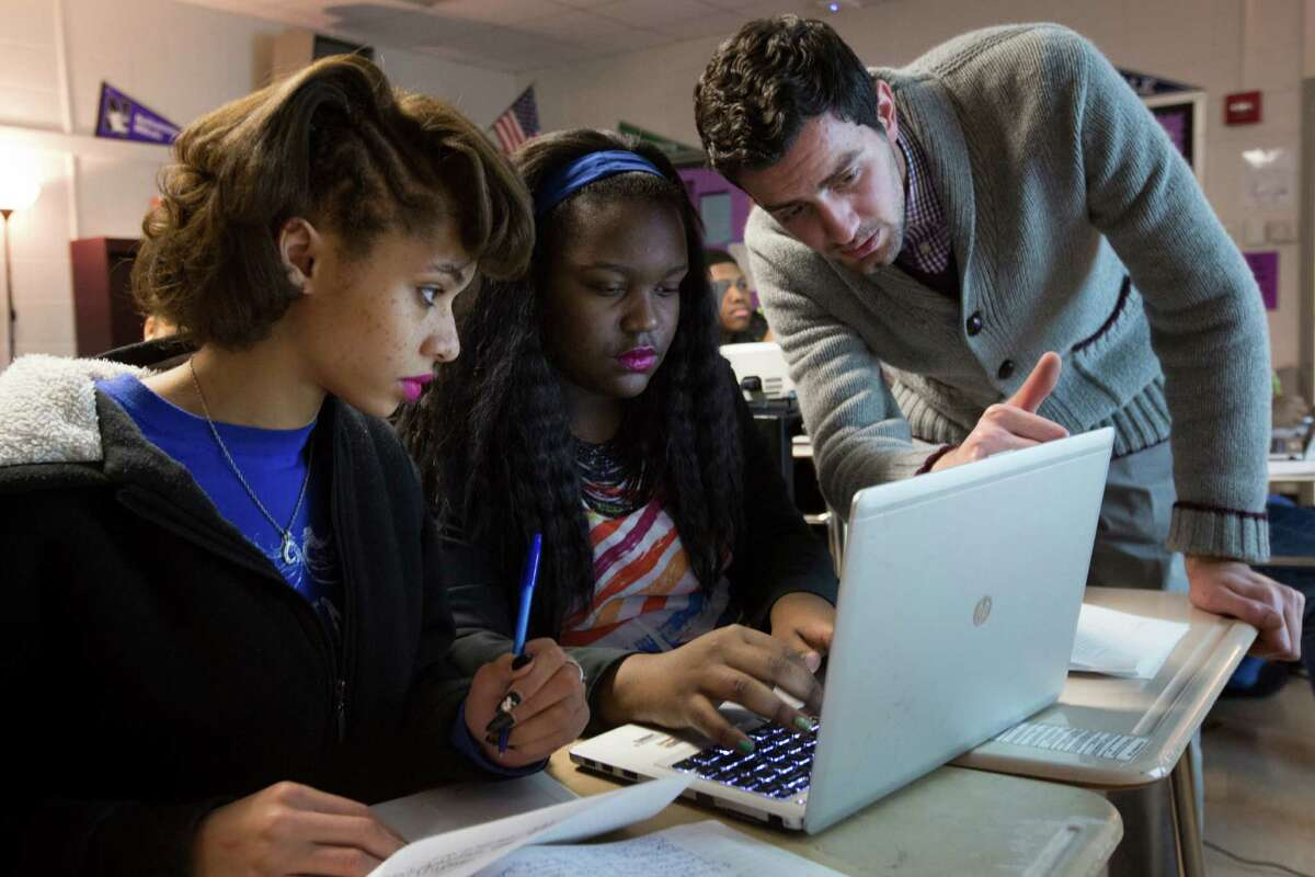 From left, Cora Desrochers, 18, and Viaginae Edmond, 16, take instruction from Kashmere High School physics teacher Adeeb Barqawi.