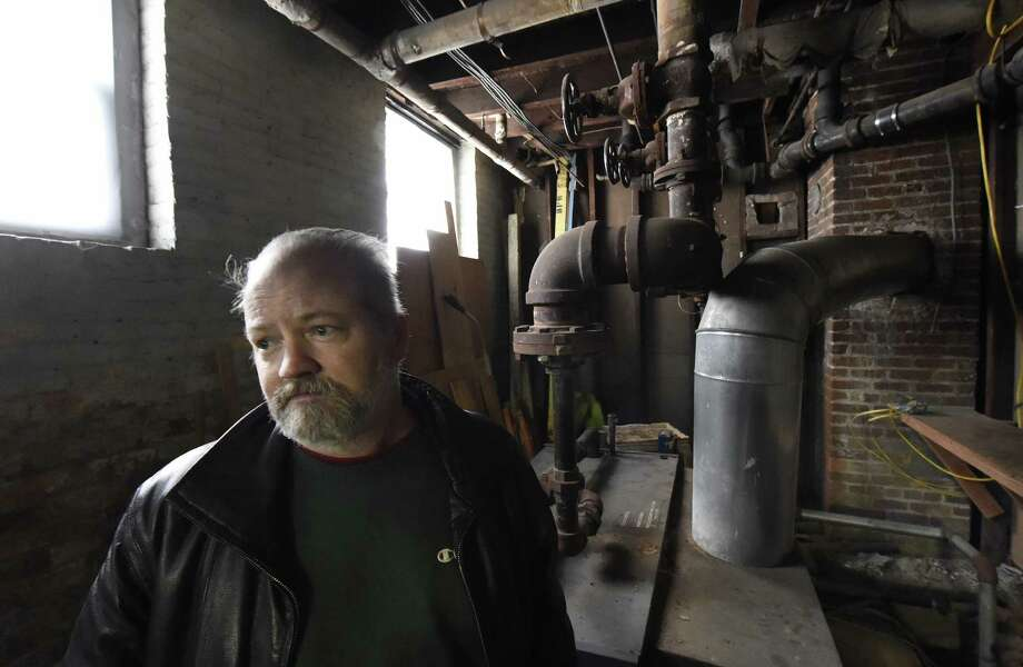 The Rev. Dave Lewis in his Troy church. The Sixth Avenue Baptist Church was damaged in January by thieves who stole copper pipes. Now, it's facing foreclosure and a $115,000 tax bill. (Skip Dickstein/Times Union) ORG XMIT: MER2015010814203571 Photo: SKIP DICKSTEIN