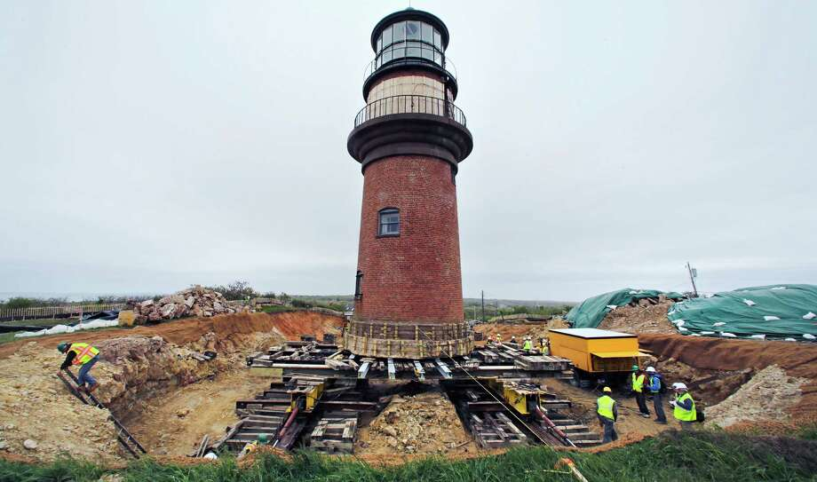 A worker climbs out of a hole dug around the Gay Head Lighthouse while moving the historic structure in Aquinnah, Mass., on the island of Martha's Vineyard, Thursday, May 28, 2015. The 160-year-old lighthouse started a multi-day trek to a new home slightly further inland.   The $3 million effort to move and save the structure was due to fear that it could tumble down a rapidly-eroding cliffside. (AP Photo/Charles Krupa) Photo: Charles Krupa, STF / Associated Press / AP