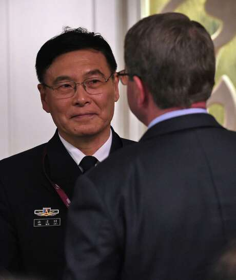 "Sun Jianguo (L) from the Chinese People's Liberation Army Navy, chats with US Secretary of Defense Ashton Carter (face back) during the ministerial luncheon at the 14th Asia Security Summit, the International Institute for Strategic Studies (IISS) Shangri-La Dialogue 2015 in Singapore on May 30, 2015. The United States on May 30 called for an ""immediate and lasting halt"" to reclamation works in disputed waters in the South China Sea, saying Beijing's behaviour in the area was ""out of step"" with international norms. AFP PHOTO / ROSLAN RAHMANROSLAN RAHMAN/AFP/Getty Images Photo: ROSLAN RAHMAN, Staff / AFP / Getty Images / AFP"
