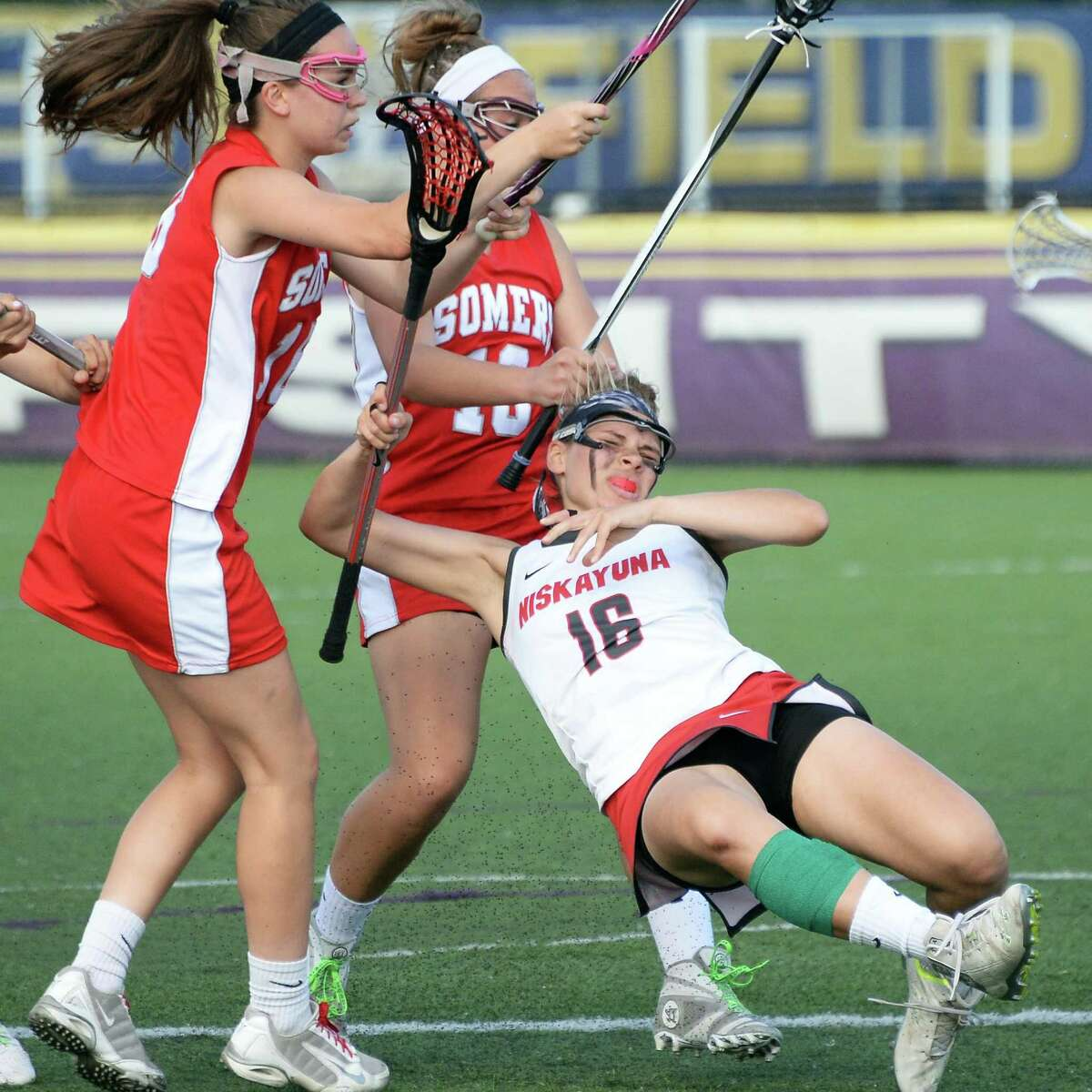 Niskayuna's #16 Alissa Franze, right, goes down amid Somers' #16 Tara Curran, left, and #10 Nina Bradbury after firing off a shot during their Class B girls' lacrosse regional final Saturday May 30, 2015 in Albany, NY. (John Carl D'Annibale / Times Union)