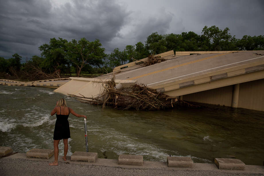 "Jill Ahrens looks at the damage to the Blanco River Bridge in Blanco, Texas on Saturday, May 30, 2015. ""It makes me sick to think about the lives lost,"" Jill Ahrens said. Photo: Carolyn Van Houten, Staff / San Antonio Express-News / 2015 San Antonio Express-News"