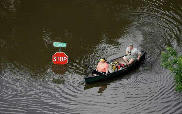 In this aerial photo, people canoe through floodwaters past a stop sign near Bear Creek Park Saturday, May 30, 2015, in Houston. The Colorado River in Wharton and the Brazos and San Jacinto rivers near Houston are the main focus of concern as floodwaters move from North and Central Texas downstream toward the Gulf of Mexico. (AP Photo/David J. Phillip) ORG XMIT: TXDP108 Photo: David J. Phillip / AP