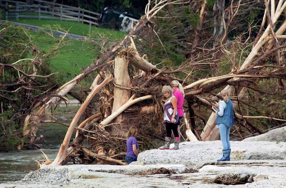 Cara Hewitt, from left, Linda Balas and Kathy Bullard see where in Wimberley their friends were swept away. Photo: Jay Janner, MBO / Austin American-Statesman