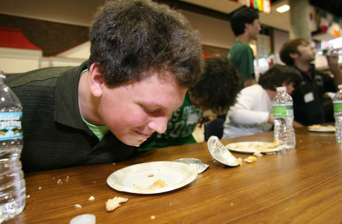 Greenwich High School student Luke Hoefer finishes off the last piece of his pie during a pie eating contest which was part of Friday's House Olympics, a day long competition between the school's five houses that includes dodge ball, hula hoops, and simon says contests, organized by the student government to foster school spirit.