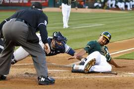 OAKLAND, CA - MAY 30:  Marcus Semien #10 of the Oakland Athletics is tagged out at home plate by Brian McCann #34 of the New York Yankees in front of umpire Dana DeMuth #32 during the first inning at O.co Coliseum on May 30, 2015 in Oakland, California. (Photo by Jason O. Watson/Getty Images)