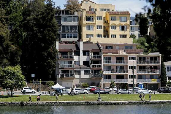 Neighbors across the street from Lake Merritt, had complained in the past when barbecues would send smoke to the upper levels of their homes, as seen on Sat. May 30, 2015, in Oakland, Calif. Regular patrols by the Oakland Police Department over the weekends has cut down on the use of barbecues .