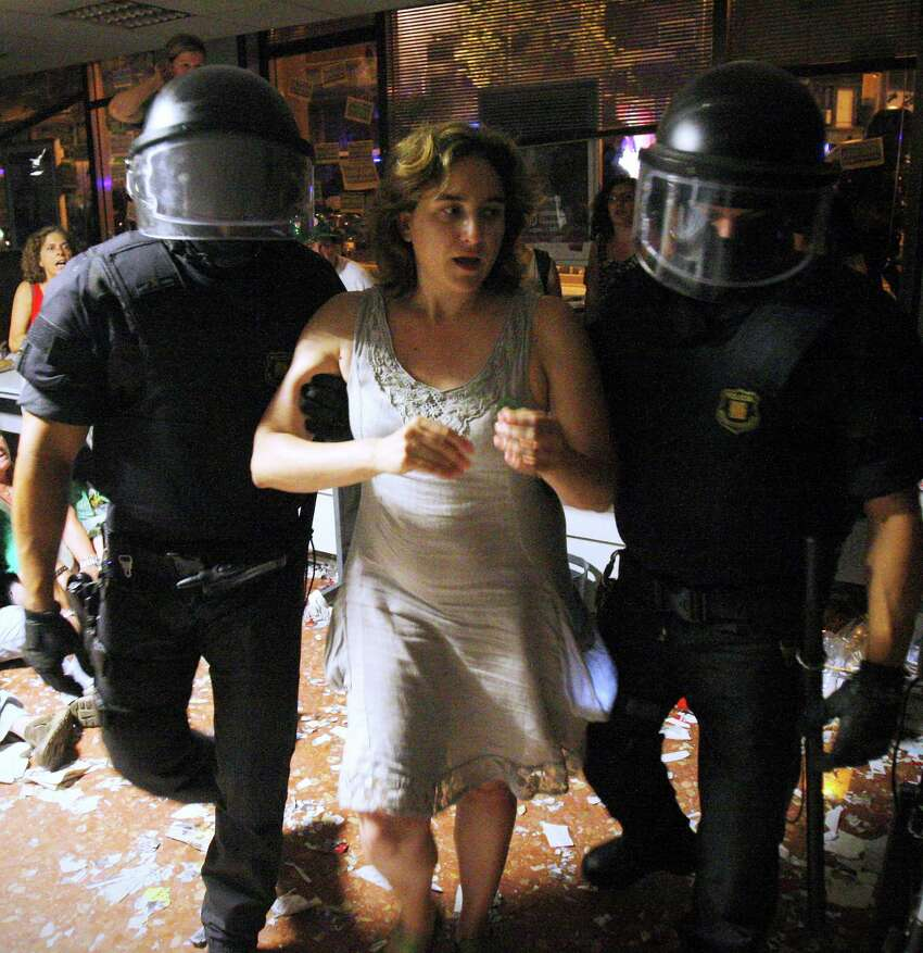 In this Friday July 26, 2013 photo, leading Spanish social activist Ada Colau, center, who beat the candidate of the Catalonia region's long-dominant conservative Convergence and Union party in Sunday's local elections in Spain, is escorted out by riot police officers after occupying a bank in Barcelona, Spain. Colau says the fight against evictions, poverty and corruption will be her priority as new mayor of the country's second city, Barcelona.