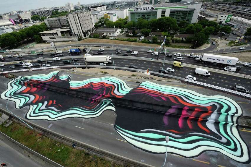 A street painting, suggesting a 3D portal, by German street artist called 1010 is pictured near the Paris bypass, France, Friday, May 29, 2015. 1010 has similar spray paintings in different cities around the world.