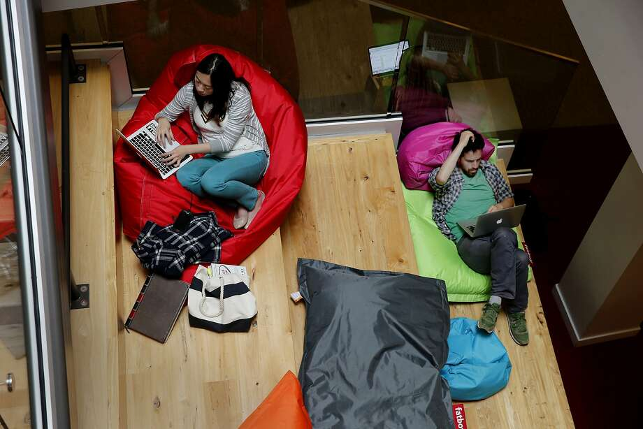 A pair relaxes on large colorful pillows provided by the lab below the coffee bar area Thursday May 28, 2015. A tour of Capital One's innovation lab for Office Space includes a variety of private spaces, meeting areas and a comfortable space for innovation and start ups next to a coffee bar. Photo: Brant Ward, The Chronicle