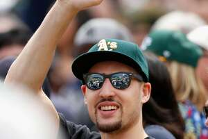Klay Thompson sits behind A's dugout - Photo