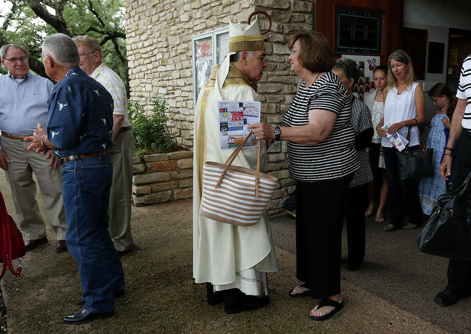 "Diocese of Austin Bishop Joe S. Vasquez greets St. Mary's Catholic Church parishioners after a service in Wimberley, Texas, Sunday, May 31, 2015. Also, volunteers search the Blanco River off Red Hawk Road northeast of Wimberley. Vasquez' message on the tragic flood was, ""Turn to God at this moment. This is a time when we all have to face the reality of the loss of loved ones, the loss of property, the loss of people who are close to us. We're family, we have to take care of one another"". Photo: JERRY LARA, San Antonio Express-News / © 2015 San Antonio Express-News"
