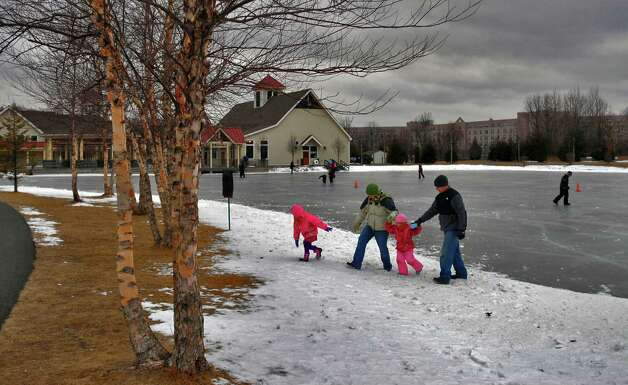 Nadia and Randy Stachowitz of Troy, second from left and far right, respectively, come off the ice with their daughters Zoeryana, 6, (cq) far left, and  and  Lilya (cq), 4, second from right, after Lilya's first time on skates on the ice, at The Crossings of Colonie park in Colonie, NY Sunday  February 14, 2010. Skating is allowed weather permitting. (Philip Kamrass / Times Union) Photo: PHILIP KAMRASS, ALBANY TIMES UNION / 00007556A