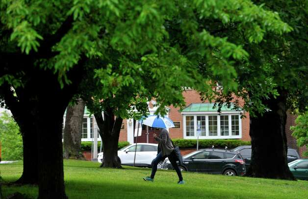A woman uses an umbrella to shield herself from rain on Monday, June 1, 2015, in Albany, N.Y.    (Paul Buckowski / Times Union)