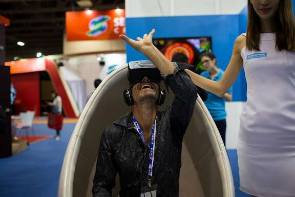 A man reacts while trying on an Oculus VR Inc. virtual reality headset at the Topgame Technology Corp. booth at the Global Gaming Expo (G2E) inside the Venetian Macau resort and casino, operated by Sands China Ltd., a unit of Las Vegas Sands Corp., in Macau, China, on Tuesday, May 19, 2015. The gaming expo runs through May 21. Photographer: Billy H.C. Kwok/Bloomberg