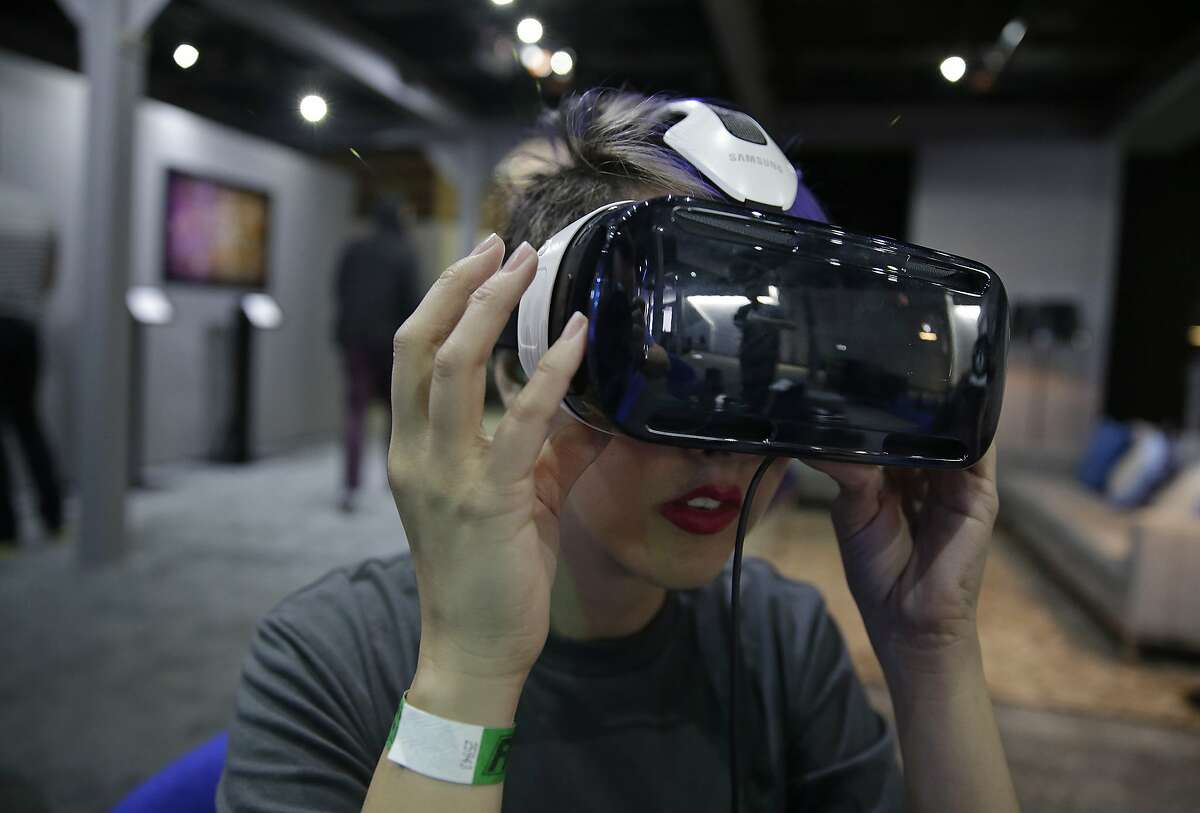 In this March 26, 2015 photo, a woman demonstrates the Oculus virtual reality headset at the Facebook F8 Developers Conference in San Francisco. Once seen as mainly a tool for alien-blasting video gamers, now major movie studios, television producers and even budding artists are adopting the technology that has users donning bulky goggles, entering house-sized domes, even rigging their smartphones to immerse themselves in faraway realms. (AP Photo/Eric Risberg)