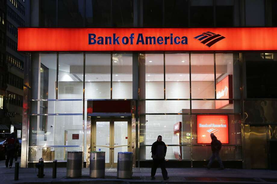 In this Jan. 14, 2015 photo, people walk past a branch of Bank of America, in New York. The Federal Reserve on Wednesday, March 11, 2015 announced it is ordering Bank of America to revise its plans for increasing dividends or buying back stock, saying there are gaps in its risk planning. (AP Photo/Mark Lennihan) Photo: Mark Lennihan, Associated Press