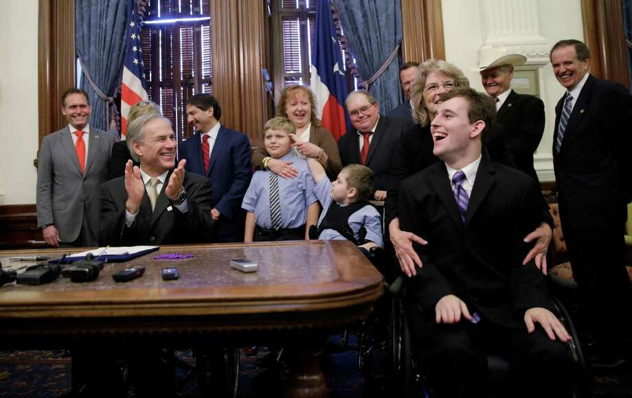 Zachariah Moccia, right, who has dravet syndrome,  celebrates after Texas Gov. Greg Abbott, front left, signed SB 339, a bill allowing the medical use of low-THC cannabis, into law at the Texas Capitol, Monday, June 1, 2015, in Austin, Texas. (AP Photo/Eric Gay) Photo: Eric Gay, Associated Press / AP