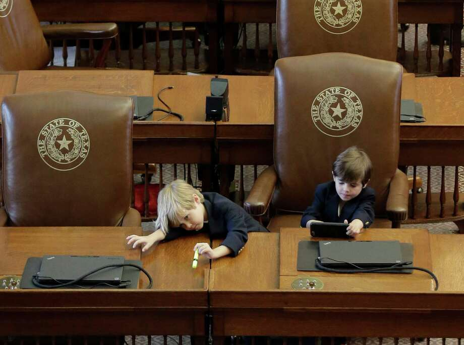 Ford Phelan, 6, and his brother Mack, 5, sit at the desk of their father, Rep. Dade Phelan, R- Port Neches, during the final day of the legislative session in the House chamber at the Texas Capitol, Monday, June 1, 2015, in Austin, Texas. Guns, tax cuts and border security: new Republican Gov. Greg Abbott made those priorities his first six months on the job, and after the Texas Legislature ends Monday, he'll claim plenty of victories. (AP Photo/Eric Gay) Photo: Eric Gay, Associated Press / AP