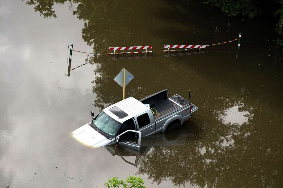 An abandoned truck sits stuck in floodwaters near Bear Creek Park on Saturday, May 30, 2015, in Houston. ( Brett Coomer / Houston Chronicle )