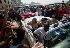 Fans take photographs of pop artist Rihanna, center,  as she rides on an American classic car after a photo shoot with photographer Annie Leibovitz at a building on the Malecon, in Havana, Cuba, Friday, May 29, 2015. (AP Photo/Desmond Boylan)