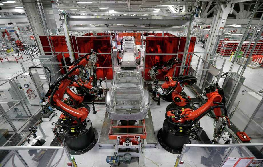 In this May 14, 2015 photo, Kuka robots work on Tesla Model S cars in the Tesla factory in Fremont, Calif. The Institute for Supply Management, a trade group of purchasing managers, issues its index of manufacturing activity for May on Monday, June 1, 2015. (AP Photo/Jeff Chiu) ORG XMIT: NYBZ162 Photo: Jeff Chiu / AP