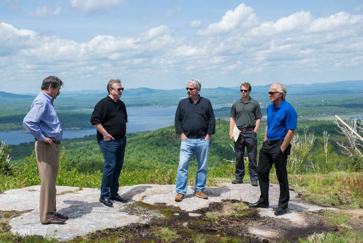 Famous golfer Greg Norman, rightt, meets with Adirondack Club and Resort developer Tom Lawson, left, and other officials, atop Big Tupper Ski Area last week. Norman is taking a hand in the project.