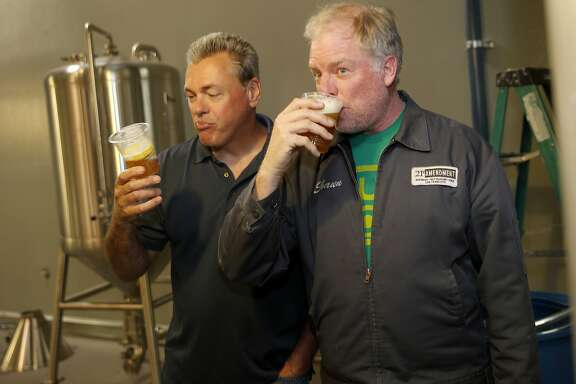 Owners Nico Freccia (left) and Shaun O'Sullivan enjoy a sip of their first IPA brewed at the new facility Monday June 1, 2015. 21st Amendment Brewery is opening a massive and ambitious multi-million dollar facility in San Leandro, Calif. at the site of the former Kellog Cereal factory.
