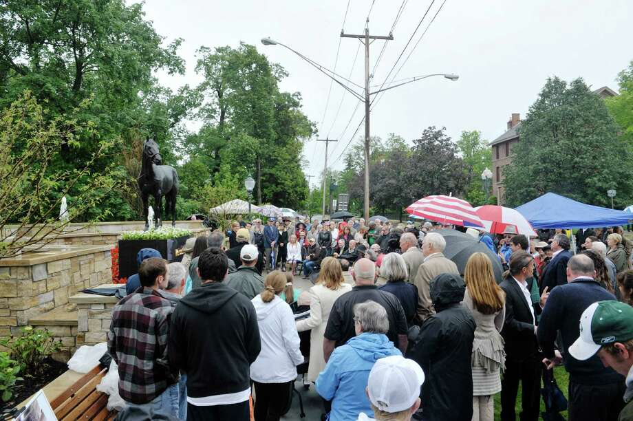 People gather for a dedication ceremony for Centennial Park on Monday, June 1, 2015, in Saratoga Springs, N.Y.  The horse statue, which is of the horse Storm Cat, will be replaced with a statue of Native Dancer with jockey aboard the horse once the statue is complete.  (Paul Buckowski / Times Union) Photo: PAUL BUCKOWSKI / 00032098A