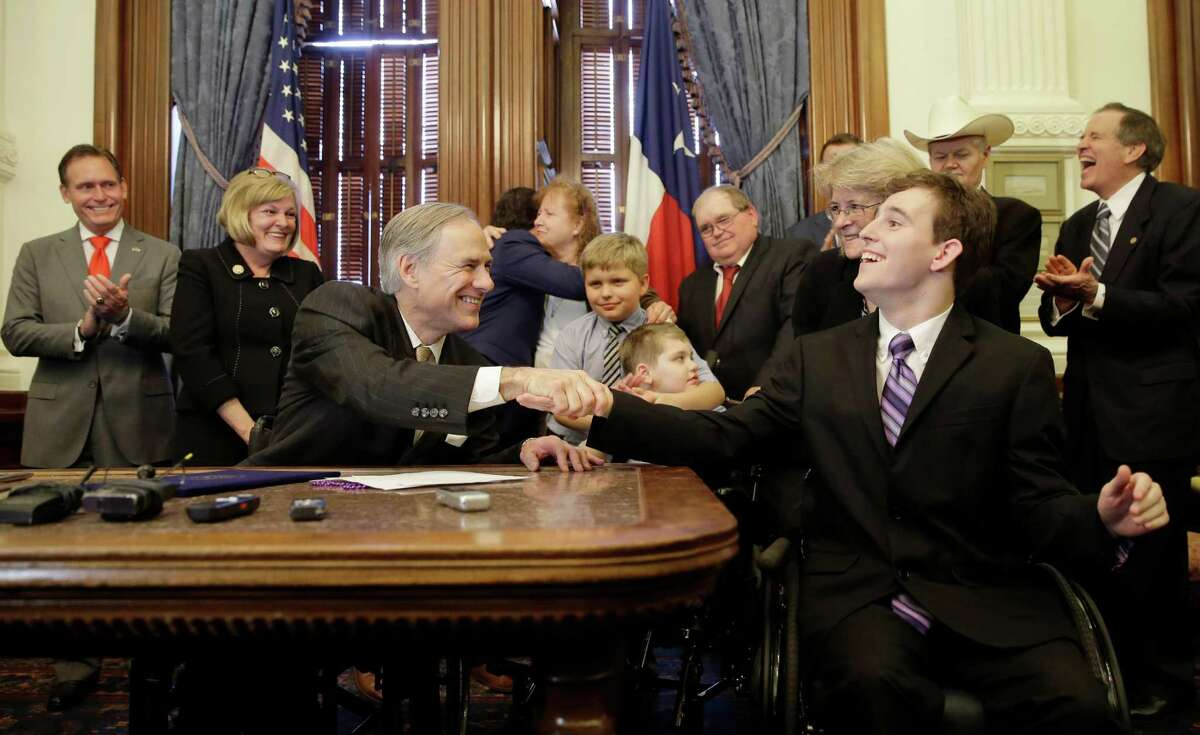Texas Gov. Greg Abbott, front left, shakes hands with Zachariah Moccia, right, who has dravet syndrome, after he signed SB 339, a bill allowing the medical use of low-THC cannabis, into law at the Texas Capitol, Monday, June 1, 2015, in Austin, Texas. (AP Photo/Eric Gay)