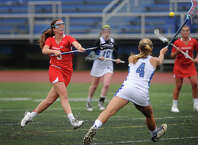 Greenwich's Katie Harford scores a goal as Fairfield Ludlowe defender Emily Demaso attempts to intercept the shot in the opening round of the girls lacrosse state tournament in Fairfield, Conn. on Monday, June 1, 2015.