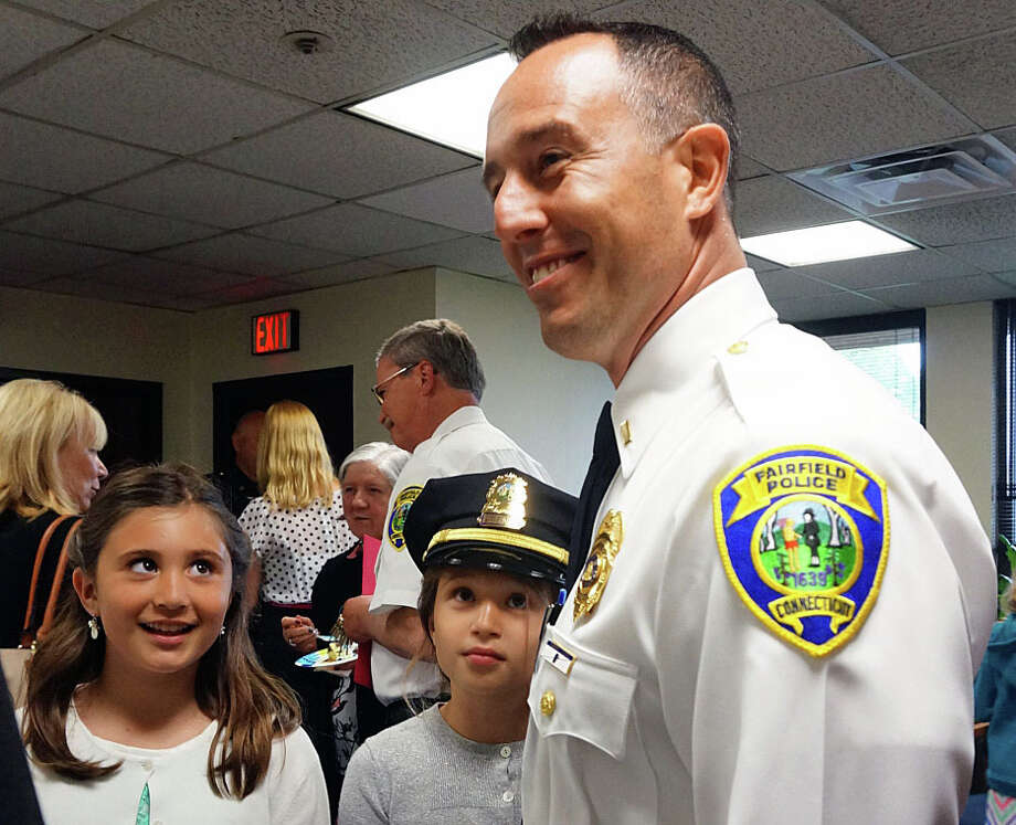 Elyssa, 8, and Marin, 9, smile up at their dad, Lt. Robert Kalamaras after his promotional ceremony Monday at police headquarters. Photo: Genevieve Reilly / Fairfield Citizen