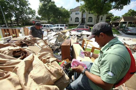 Nicolas Pérez and Marbin Zelaya on Monday examine the damage done to a Braeswood residence. The city's Web-based system to be launched Tuesday will let volunteers search a map for needs they can help satisfy.