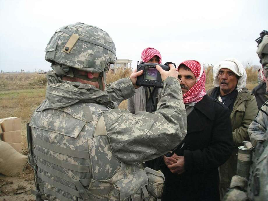 An American soldier captures iris images from civilians to search for the true identity of a detainee against individuals contained in watchlists. Photo: Contributed Photo / Stamford Advocate Contributed