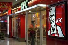 TIANJIN, CHINA - 2015/02/24: A customer walks into a KFC restaurant.  KFC restaurants in China will start selling freshly ground coffee in 2015 to become a lower-cost premium alternative to Starbucks. The initiative began earlier this year and is expected to perform in 2,500 KFCs in China by the end of this year.