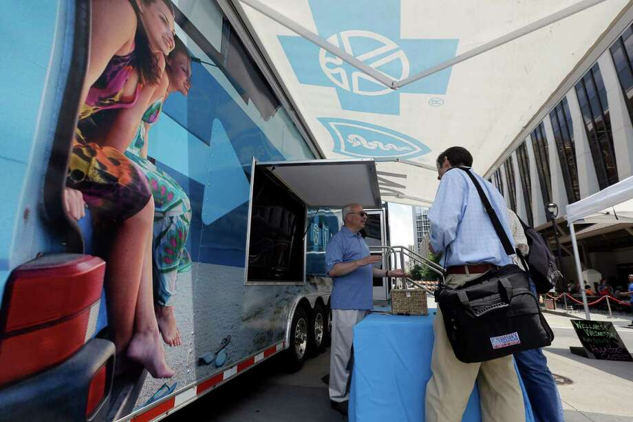 FILE - In this photo taken Wednesday, July 17, 2013, Blue Cross Blue Shield of North Carolina employee Lew Borman, left, helps a customer outside a trailer at the downtown farmer's market in Raleigh, N.C. Dozens of health insurers say higher-than-expected care costs and other expenses blindsided them this year, and they're going to have to hike individual insurance prices well-beyond 10 percent for 2016. (AP Photo/Gerry Broome, File) ORG XMIT: NYBZ169 Photo: Gerry Broome / AP