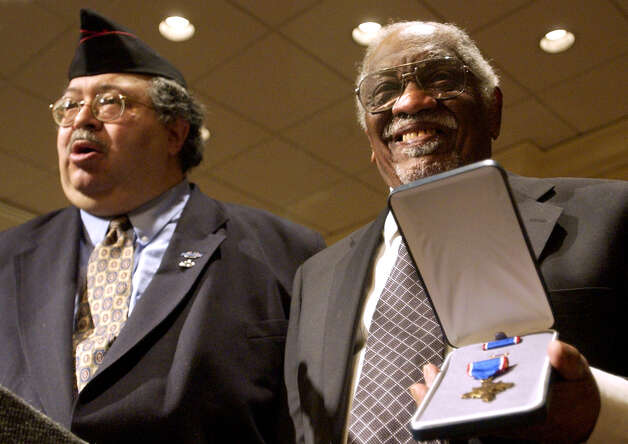 Herman Johnson, right, holds the Distinguished Service Cross awarded to Sgt. Henry Johnson during a ceremony Feb. 16, 2003, at Crown Plaza Hotel in Albany. John Howe, a key figure in the recognition of Henry Johnson's actions during WWI, recognizes participants. (Will Waldron/Times Uniona archive) Photo: WILL WALDRON / j=0321_henryjohnson