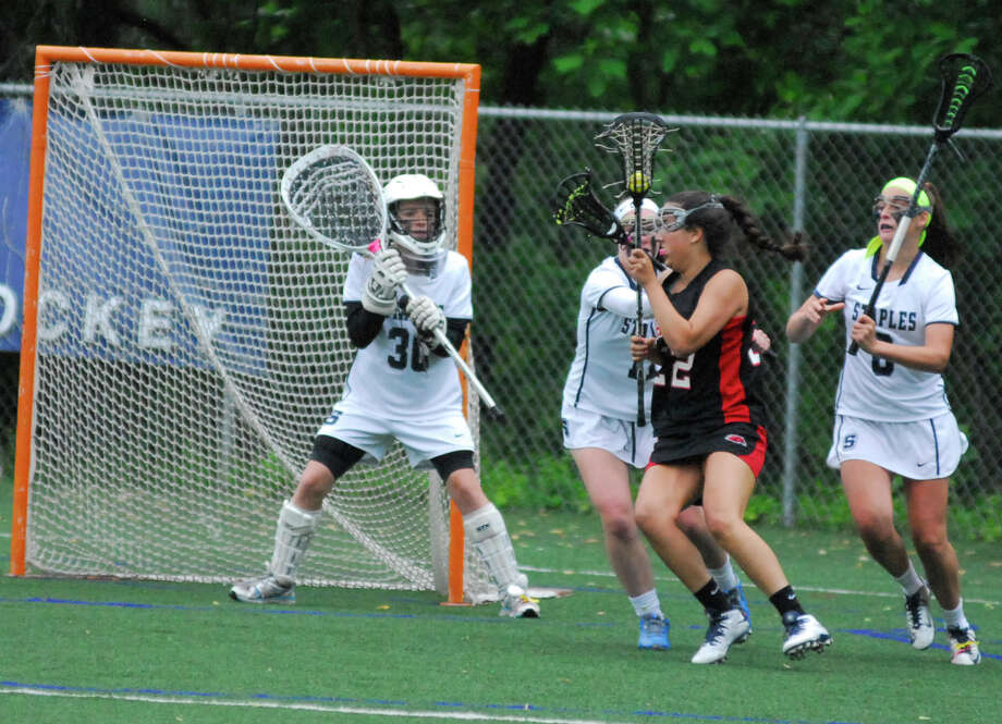 Fairfield Warde's Clare Secrist, second from right, tries to fight through the Staples defense while goalie Emma Boland, left, looks on during a Class L girls lacrosse game on Monday, June 1 2015 in Westport, Connecticut. Staples won 11-8. Photo: Ryan Lacey/Staff Photo / Westport News Contributed