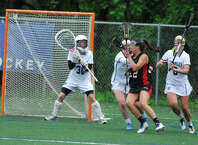 Fairfield Warde's Clare Secrist, second from right, tries to fight through the Staples defense while goalie Emma Boland, left, looks on during a Class L girls lacrosse game on Monday, June 1 2015 in Westport, Connecticut. Staples won 11-8.