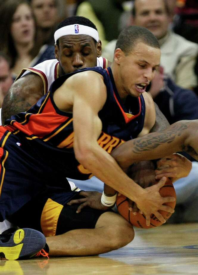 In this Nov. 17, 2009, file photo, Golden State Warriors' Stephen Curry, right, scrambles for possession with Cleveland Cavaliers' LeBron James, left, during the fourth quarter of an NBA basketball game in Cleveland. James and Curry both hail from Akron, Ohio, the Rubber City best known for tires and now for producing a pair of bouncing baby basketball prodigies. (AP Photo/Mark Duncan, File) ORG XMIT: NY151 Photo: Mark Duncan / AP