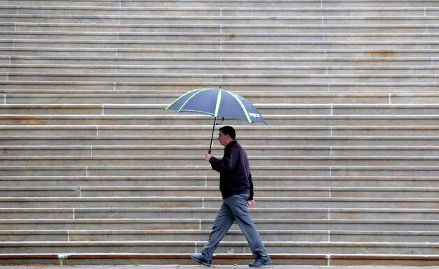 The Capitol steps provides a background of parallel lines for an umbrella-clad gentleman shielding himself from the rain Monday afternoon, June 1, 2015, in Albany, N.Y. (Will Waldron/Times Union) Photo: WW