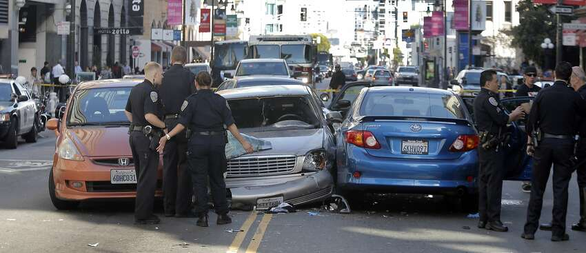 SFPD officers gather evidence at the scene of a car crash after a wanted parolee led officers on a chase from the Bayview district to Market Street and Fifth Street where he crashed his car into several vehicles before being stopped and apprehended in San Francisco, Calif., on Monday, June 1, 2015. There were two minor injuries from the accident and both were transported to the hospital.