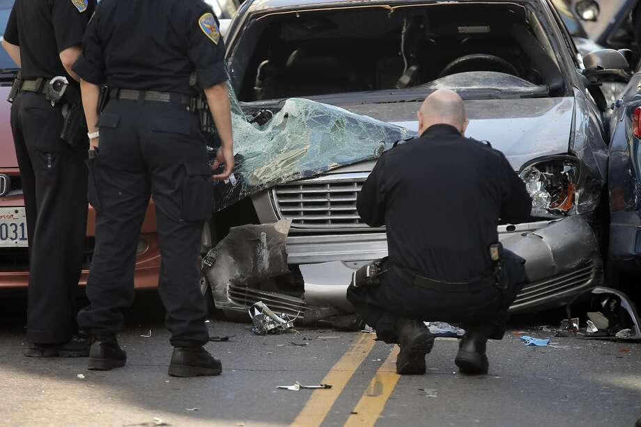SFPD officers gather evidence at the scene of a car crash after a wanted parolee led officers on a chase from the Bayview district to Market Street and Fifth Street where he crashed his car into several vehicles before being stopped and apprehended in San Francisco, Calif., on Monday, June 1, 2015. There were two minor injuries from the  accident and both were transported to the hospital. Photo: Carlos Avila Gonzalez, The Chronicle