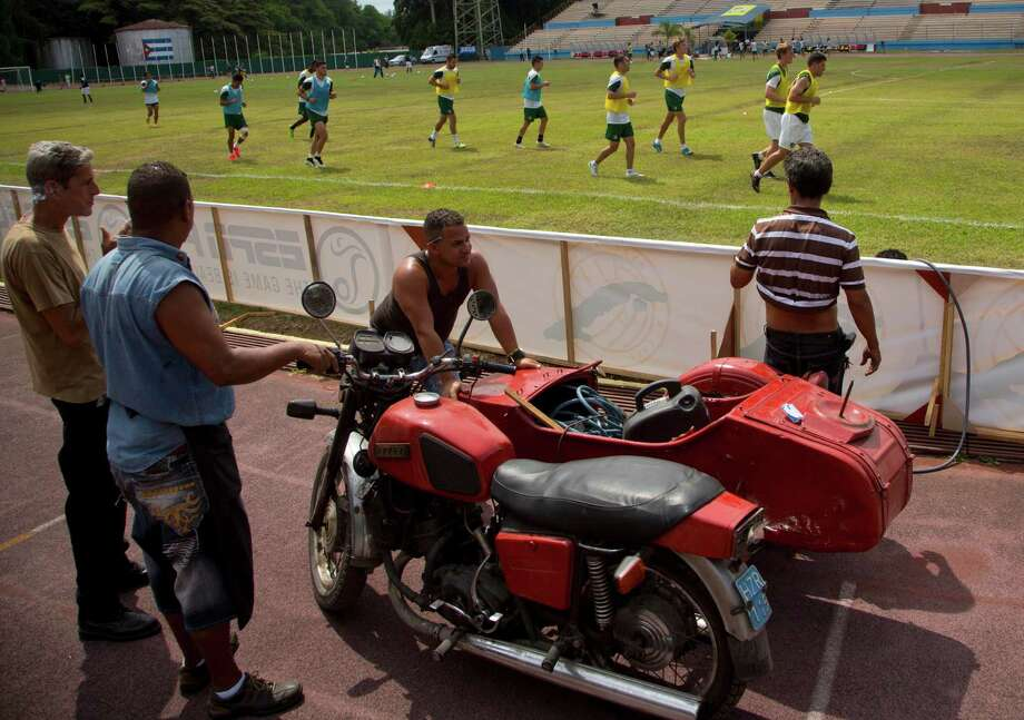 Stadium workers use an old Russian motorcycle with a sidecar, which they use to transport tools at the Pedro Marrero stadium, as New York Cosmos soccer players train for a friendly against Cuba's national team, in Havana, Cuba, Monday, June 1, 2015. On Tuesday, the team will become the first U.S. professional team to play in Cuba since Presidents Raul Castro and Barack Obama announced that they were re-establishing diplomatic relations. (AP Photo/Ramon Espinosa) ORG XMIT: XRE101 Photo: Ramon Espinosa / AP
