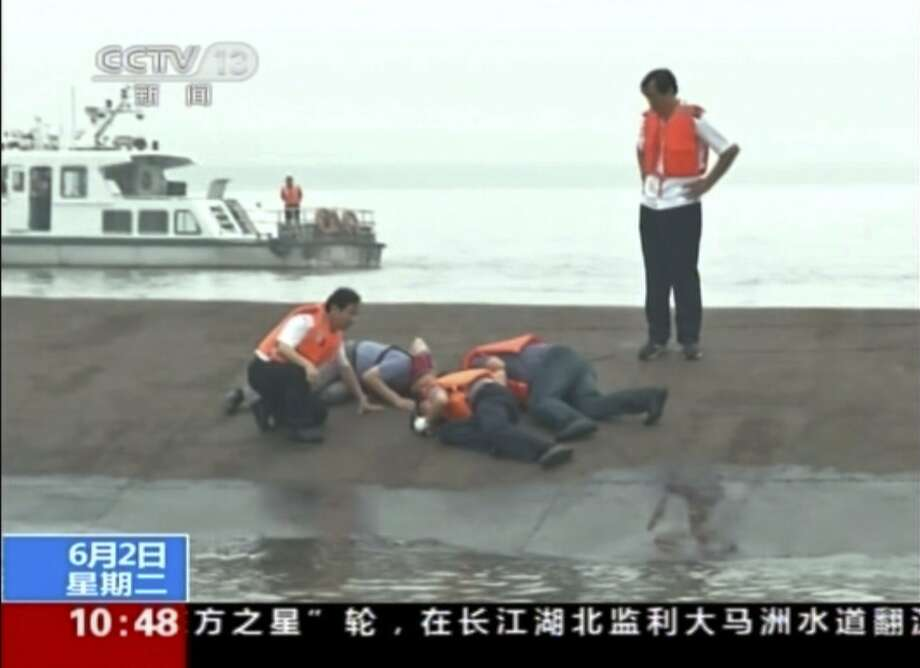 """In this image taken from video released by China's CCTV, rescue workers listen for a response to their tapping on the hull of a capsized ship on the Yangtze River in central China's Hubei province Tuesday, June 2, 2015. The small cruise ship sank overnight in China's Yangtze River during a storm, state media said Tuesday.  Chinese words on the bottom read """"Ferry capsize on Yangtze.""""  (CCTV via AP Video) CHINA OUT, NO SALES, NO ARCHIVES, EDITORIAL USE ONLY Photo: Associated Press"""
