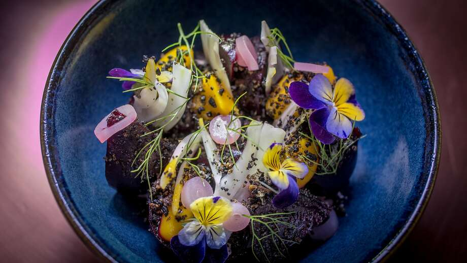 The boldly flavored dish of pickled beets and kumquats ($10) is set on a Idiazabal custard blanketed with black olives, shaved fennel and viola blossoms. Photo: John Storey, Special To The Chronicle