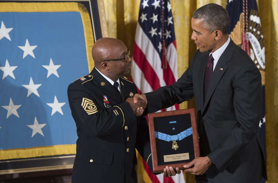 US President Barack Obama presents the Medal of Honor to Command Sergeant Major Louis Wilson of the New York National Guard, who is accepting on behalf of the late Army Private Henry Johnson, for actions while serving in France during World War I, during a ceremony in the East Room of the White House in Washington, DC, June 2, 2015. Obama also awarded a Medal of Honor to the late Army Sergeant William Shemin for his actions, also during World War I. AFP PHOTO / SAUL LOEBSAUL LOEB/AFP/Getty Images)